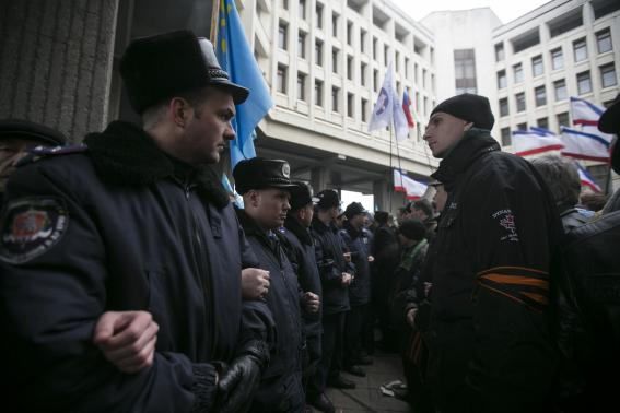 Ukrainian police separate ethnic Russians (R) and Crimean Tatars during rallies near the Crimean parliament building in Simferopol February 26, 2014. Thousands of pro-Russia separatists tussled with supporters of Ukraine's new leaders in Crimea on Wednesday as tempers boiled over the future of the region following the upheaval that swept away President Viktor Yanukovich. One person died, apparently of a heart attack, and two others were trampled and injured when people stumbled and fell to the ground in the crush, witnesses said. REUTERS/Baz Ratner