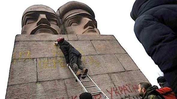 February 23, 2014: People paint on the KGB officers monument in Kiev, Ukraine. (AP Photo/Andrew Lubimov)