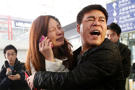 A relative of a passenger on board Malaysia Airlines flight MH370 cries