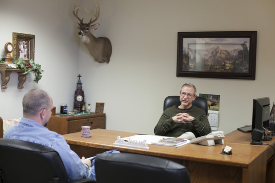 Joe Trussell is pastor of the Church of God (Holiness), the largest church in El Dorado Springs. He has traveled to many parts of the world but says, 'A lot of people here, if they get out of Cedar County it's like they've been to another country.' In his office is a trophy of a deer he shot himself. Catalin Abagiu for The Wall Street Journal