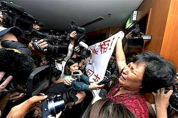 "A Chinese relative of passengers aboard a missing Malaysia Airlines plane cries as she holds a banner in front of journalists reading 'We are against the Malaysian government for hiding the truth and delaying the rescue. Release our families unconditionally!""  at a hotel in Sepang, Malaysia, Wednesday, March 19, 2014. Malaysian authorities examined new radar data from Thailand that could potentially give clues on how to retrace the course of the Malaysia Airlines plane that vanished early March 8 with 239 people aboard en route from Kuala Lumpur to Beijing. Twenty-six countries are looking for the aircraft as relatives anxiously await news. (AP Photo) MALAYSIA OUT"