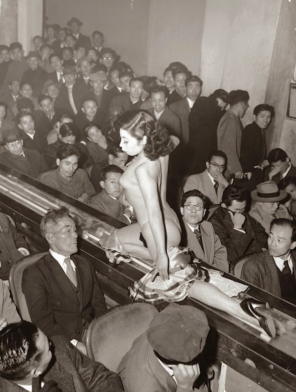 A stripper at a Tokyo striptease show is taken past the audience on a moving conveyor belt. 1957