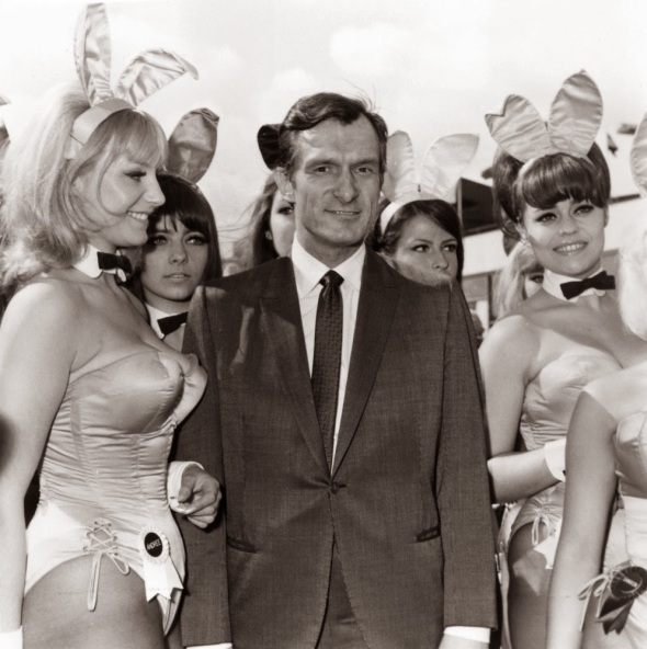 Playboy editor and tycoon Hugh Hefner is greeted by a group of bunny girls from his Playboy Clubs, upon his arrival at London Airport. (Dove / Getty Images)