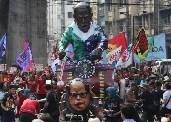 Effigies of U.S. President Barack Obama riding a cart and Philippine President Benigno Aquino III as a dog are pushed by activists during a rally outside the Malacanang presidential palace in Manila on Monday to oppose the Enhanced Defense Cooperation Agreement between the countries. | AP