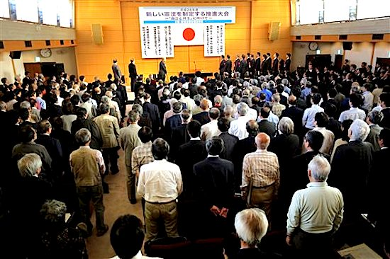 In this Thursday, May 1, 2014, guests and audience stand as they listen to the Japanese national anthem at a meeting of a pro-constitution amendment group in Tokyo. Japan is marking the 67th anniversary of its postwar constitution on May 3, 2014 with growing debate over whether to revise the war-renouncing document. Prime Minister Shinzo Abeís ruling conservative party has long advocated revision but been unable to sway public opinion. Now he proposes that the government reinterpret the constitution so it can loosen the reins on its military without having to win approval for constitutional change. (AP Photo/Eugene Hoshiko)