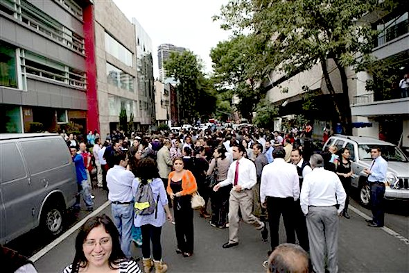 People gather in the street after an earthquake was felt in Mexico City, Thursday, May 8, 2014. A strong earthquake on the Pacific coast shook the capital, sending frightened office workers streaming into the streets away from high-rise buildings. (AP Photo/Rebecca Blackwell)