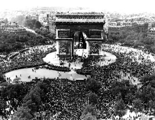 his is an aerial view of the Arc de Triomphe in Paris on VE Day, May 7, 1945, shows thousands of French people celebrating the announcement of Germany's unconditional surrender to the Allies. British, American and French servicemen mingled with the crowds who sang and danced throughout the night. (AP Photo/Griffin)