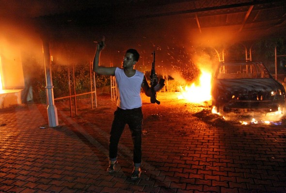 An armed man waves his rifle as buildings and cars are engulfed in flames after being set on fire inside the US consulate compound in Benghazi late on Sept. 11, 2012. The alleged ringleader in the attack has been captured by involving Special Operations forces. (AFP/Getty Images)