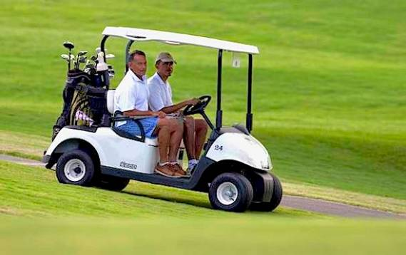 President Obama, right, rides in a golf cart with longtime friend Bobby Titcomb to the 18th green at Mid-Pacific County Club in Kailua, Hawaii, Wednesday, Jan. 1, 2014. (AP Photo/Carolyn Kaster)