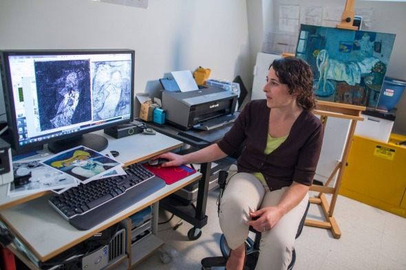 """Patricia Favero, associate conservator at The Phillips Collection, shows off an image of a man found underneath one of Picasso's first masterpieces, """"The Blue Room,"""" on Tuesday, June 10, 2014, in Washington. Image: Evan Vucci/Associated Press"""