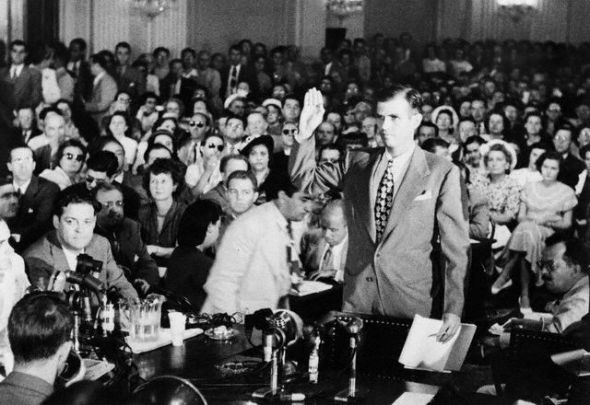 ugust 1948, Washington, DC, USA --- Alger Hiss, accused of Communist espionage, takes an oath during hearings before the House Committee on Un-American Activities.  He denied Whittaker Chambers' accusation that he was a Communist. --- Image by © Bettmann/CORBIS