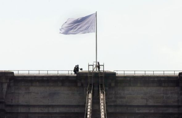 New York City Police officers stand at the base of a white flag flying atop the west tower of New York's Brooklyn Bridge, Tuesday, July 22, 2014. Two large American flags atop the Brooklyn Bridge were replaced sometime during the night with white banners. Police crime scene and intelligence detectives were investigating how the flags were switched out on the famed span that connects Brooklyn and Manhattan, and there were no reports of suspicious activity, police said. (AP Photo/Richard Drew)