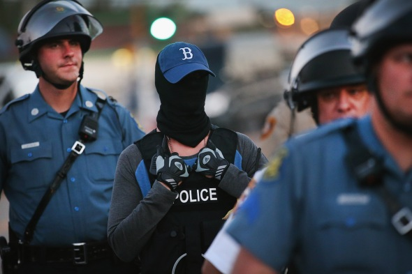 FERGUSON, MO - AUGUST 13: A police officer standing watch as demonstrators protest the shooting death of teenager Michael Brown conceals his/her identity on August 13, 2014 in Ferguson, Missouri. Brown was shot and killed by a Ferguson police officer on Saturday. Ferguson, a St. Louis suburb, is experiencing its fourth day of violent protests since the killing.  (Photo by Scott Olson/Getty Images)g