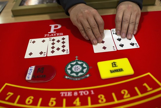 A student displays a deck of cards during a lesson at a mock casino in Macau on March 6. Casino companies are betting on Hong Kong's equity markets to raise funds for expansion. Reuters