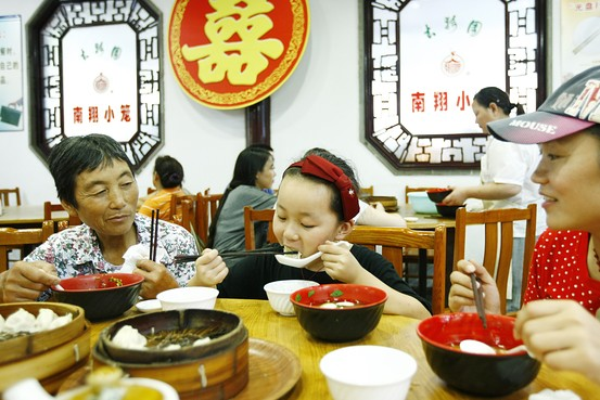 Customers eat steamed buns in a steamed buns restaurant in Shanghai, east China, Aug. 14, 2014.  Zuma Press