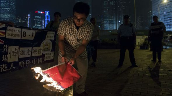 An activist burns the China's People's Liberation Army's flag to protest against the stationing of Chinese People's Liberation Army (PLA) forces in Hong Kong, at the Central Business District in Hong Kong August 1, 2014.