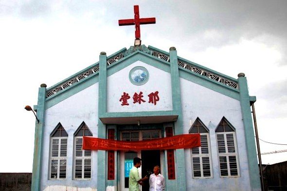 "In this photo taken July 15, 2014, Pastor Tao Chongyin, left, speaks with church member Fan Liang'an in front of the Wuxi Christian Church with the words ""Church of Jesus"" in red, in Longwan, Wenzhou in eastern China's Zhejiang province. Across Zhejiang province, which hugs China's rocky southeastern coast, authorities have toppled, or threatened to topple, crosses at more than 130 churches. ""I won't let them take down the cross even if it means they would shoot me dead,"" said Fan Liang'an, 73, whose grandfather helped build the church in 1924. (AP Photo/Didi Tang)"