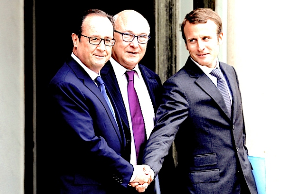 French President Francois Hollande, left, shakes hands with new French Economy Minister Emmanuel Macron while French Finance Minister Michel Sapin, centre, looks on, after the weekly cabinet meeting in Paris,on Wednesday. Remy de la Mauviniere / Associated Press