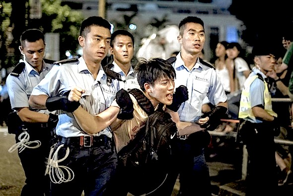 Police removed a democracy activist in Hong Kong in July. An election reform decision is expected Aug. 31.Agence France-Presse/Getty Images
