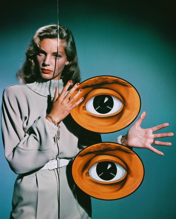 American actress Lauren Bacall poses behind a pane of glass decorated with two giant eyes, circa 1950. (Photo by Silver Screen Collection/Hulton Archive/Getty Images)