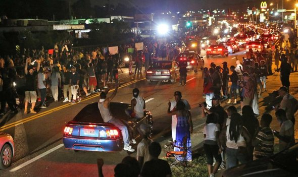 People drive down the street honking their horns, raising their arms and holding signs in Ferguson on Aug. 14. (AP Photo/St. Louis Post-Dispatch, J.B. Forbes)