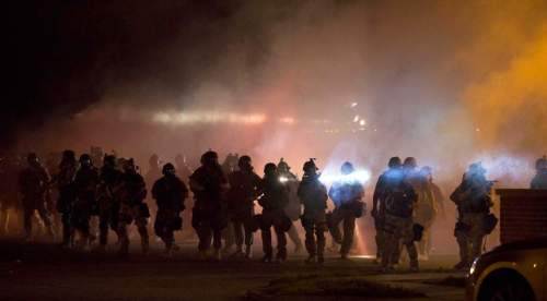 Riot police clear demonstrators from a street in Ferguson