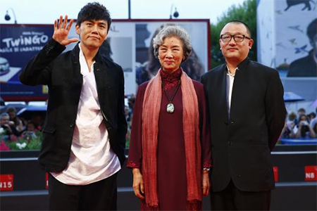 Director Wang Xiaoshuai (R) poses with cast members Qin Hao (L) and Lu Zhong during the red carpet for the movie 'Chuangru zhe' (Red amnesia) at the 71st Venice Film Festival September 4 2014.