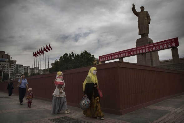 A veiled Muslim Uyghur woman walks past a statue of Mao Zedong in Kashgar in Xinjiang province. (Kevin Frayer/Getty Images)