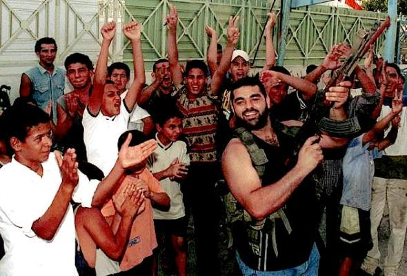 Palestinians dance in the street at the Ein el-Hilweh refugee camp near the southern port city of Sidon, Sept. 11, 2001. Palestinians in Lebanon's refugee camps celebrated the attacks in the United States by firing into the air. (AP Photo/Mohamed Zatari) Copyright 2001 The Herald-Dispatch