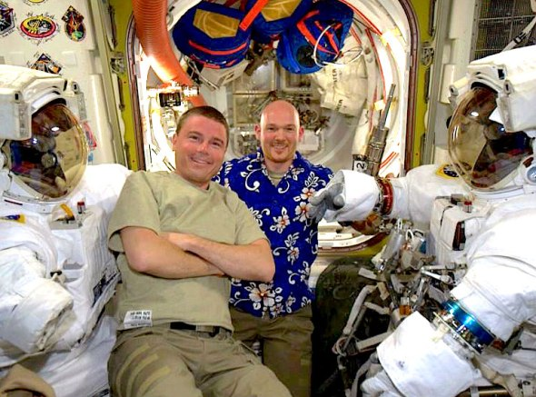 In this photo posted to Twitter by Flight Engineer Reid Wiseman, he and Flight Engineer Alexander Gerst (right) pose for a picture with spacesuits in the International Space Station's Quest airlock. Image Credit: NASA View tweet from @Astro_Reid