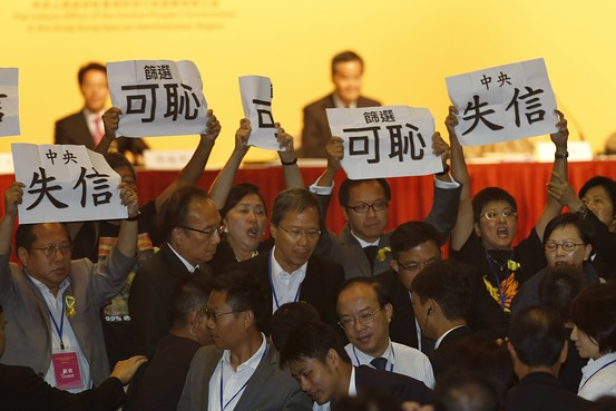 Pro-democracy lawmakers display placards against Li Fei, deputy secretary general of the National People's Congress' Standing Committee, during a briefing session in Hong Kong Monday, Sept. 1, 2014.  Associated Press