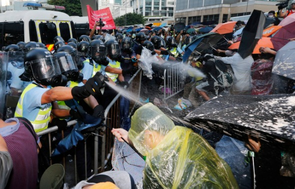 Riot policemen use pepper spray during clash with protesters, as tens of thousands of protesters block the main street to the financial Central district outside the government headquarters in Hong Kong