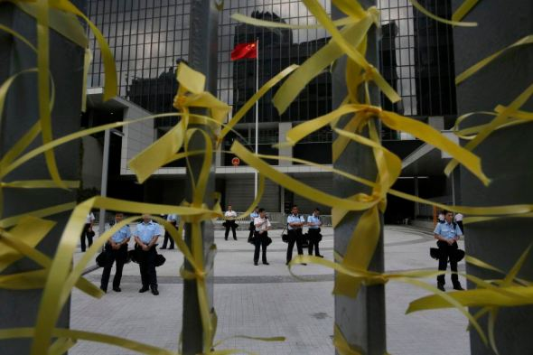 Police officers stand guard against yellow ribbons tied by protesters inside the government headquarters in Hong Kong, Sunday, Sept. 28,