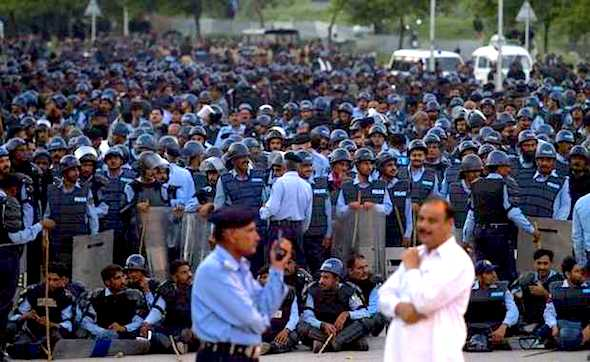 Pakistani policemen wearing riot gear standby in case of violence near the protest venue of Pakistan's fiery Muslim cleric Tahir-ul-Qadri near the parliament building in Islamabad, Pakistan, Saturday, Aug 30, 2014. ANJUM NAVEED — AP  Read more here: http://www.thestate.com/2014/08/30/3650276/pakistan-protesters-march-on-pms.html#storylink=cpy