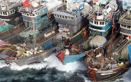 South Korean coastguards search Chinese fishermen vessels during a crackdown on their alleged illegal fishing in South Korean waters in November 2011