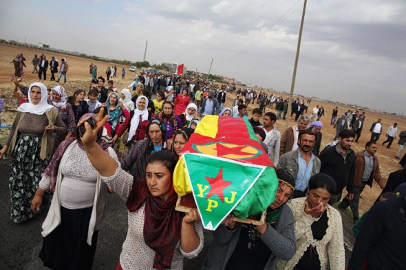 Caskets holding the bodies of four female Kurdish fighters are carried from a hospital in Suruc, Turkey, to a cemetery near the border with Syria. Andrew Quilty for The Wall Street Journal