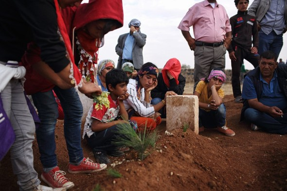 Loved ones grieve over the grave of a Kurdish fighter at a cemetery in Suruc, Turkey, across the border from the embattled Syrian city of Kobani. Andrew Quilty for The Wall Street Journal