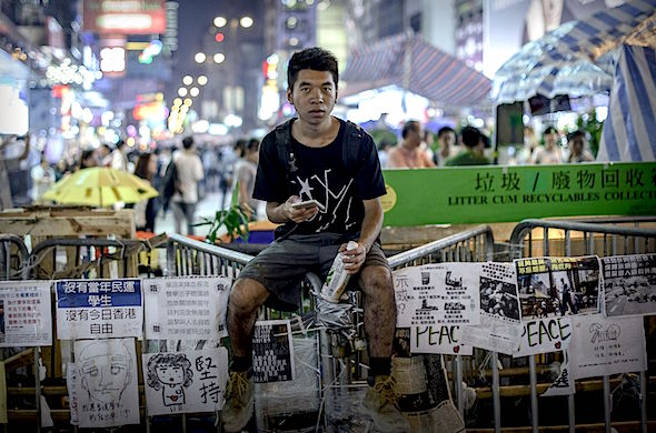 A pro-democracy protester sits on a barricade at a protest site in the Mongkok district of Hong Kong on October 26, 2014. Four weeks after tens of thousands of Hong Kongers took to the streets demanding free leadership elections for the semi-autonomous Chinese city, weary demonstrators remain encamped across several major roads.   AFP PHOTO / Philippe LopezPHILIPPE LOPEZ/AFP/Getty Images
