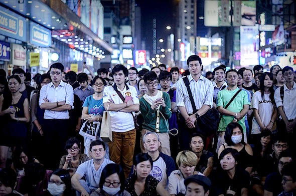 People listened to talks between student leaders and senior government officials as they were broadcast live at a protest site in the Mong Kok district of Hong Kong, Oct. 21, 2014. PHILIPPE LOPEZ/AGENCE FRANCE-PRESSE/GETTY IMAGES