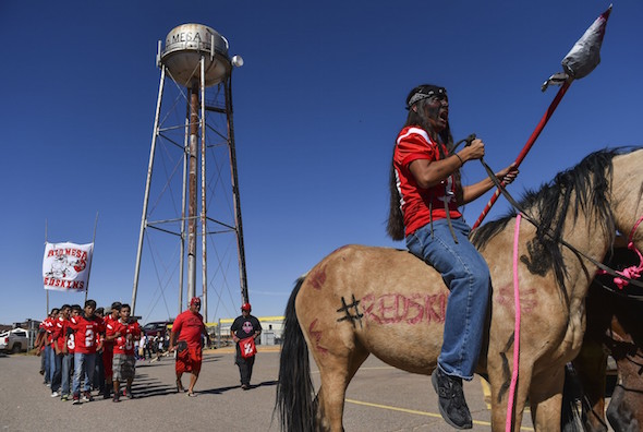 Red Mesa High School football player Kai Lameman leads the team on a march during a homecoming parade Oct. 16. (Ricky Carioti/The Washington Post)