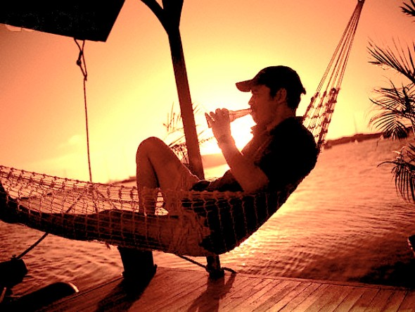 Man Relaxing in Hammock with Beer, Sunset