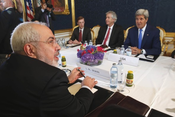 Iran's Foreign Minister Mohammad Javad Zarif, foreground left, met with U.S. Secretary of State John Kerry, background right, in Vienna in July. JIM BOURG