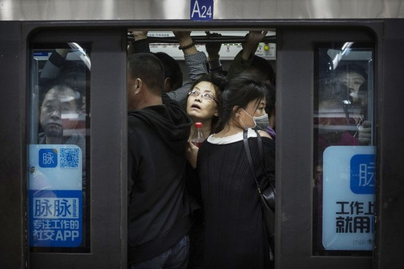 Commuters in Beijing crowd onto a subway car during rush hour last month.Getty Images