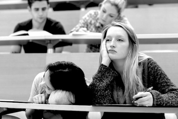 Demotivated students sitting in a lecture hall with one girl napping in college