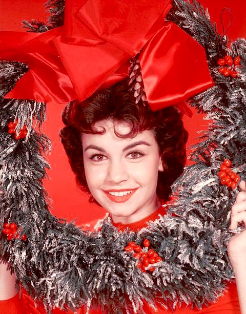 Headshot portrait of American actor and singer Annette Funicello, posing with her head encircled by a decorative Christmas wreath, circa 1955. There is a large ribbon above her head. (Photo by Hulton Archive/Getty Images)