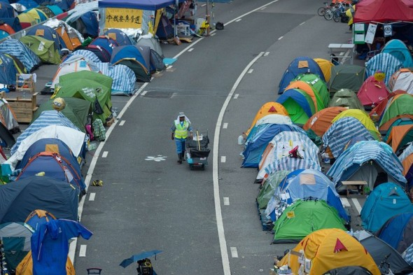 A street cleaner pushes her cart between rows of tents at the pro-democracy movement's main protest site in Hong Kong's Admiralty district. Agence France-Presse/Getty Images