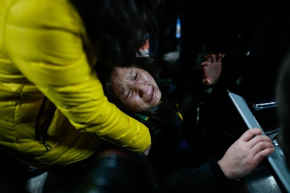 A family member (C) cries on a bench at a hospital where some of the victims of a stampede by new year's revellers were sent in Shanghai on January 1, 2015. A stampede by New Year's revellers in Shanghai's historic riverfront area killed 35 people and injured dozens more, the city government said on January 1.   CHINA OUT   AFP PHOTO        (Photo credit should read STR/AFP/Getty Images)