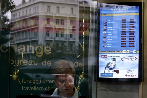 The euro tumbled to a nine-year low Monday as new worries flared over Greece, where a woman in Athens passed a currency-changing business. Associated Press