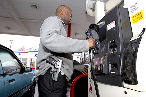 "In a Thursday, Jan. 12, 2012 photo, Rick Ector carries his Smith and Wesson 9mm as he prepares to pump gas in Detroit. Ector is pushing to make Detroit an ""open carry"" city and organizes public dinners and picnics where each legally licensed attendee wears a handgun. (AP Photo/Carlos Osorio)"