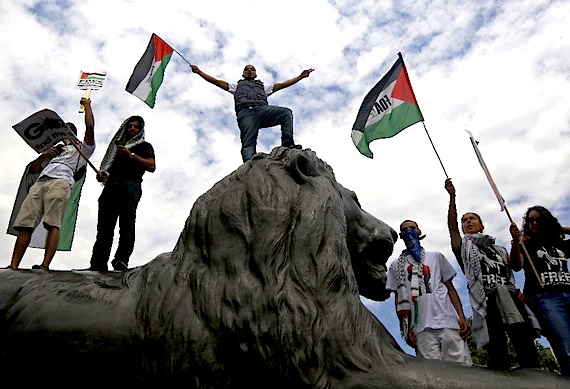 Anti-Israel demonstrators atop a Trafalgar lion (Luke MacGregor/Reuters )
